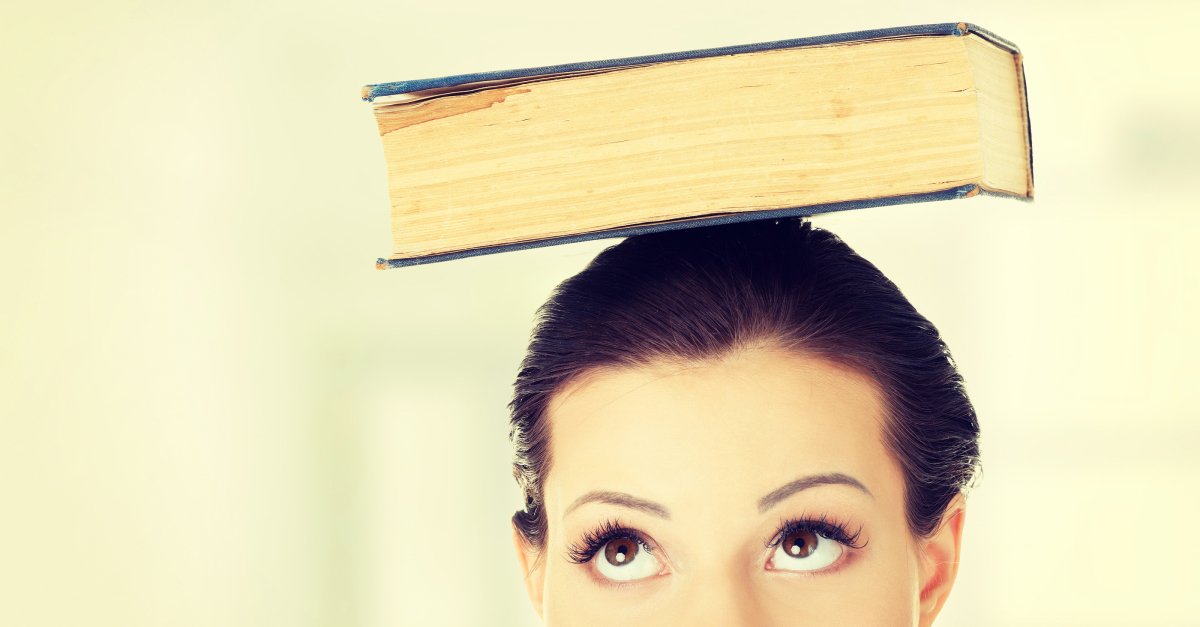 Attractive young student woman with book on head